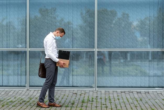 Ontslag wegens een coronavirusepidemie. ontslagen werknemer verlaat het kantoor met zijn kantoorbenodigdheden.