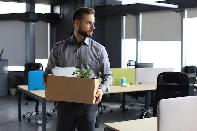 Ontslagen werknemer die van kantoor gaat met zijn kantoorbenodigdheden.
