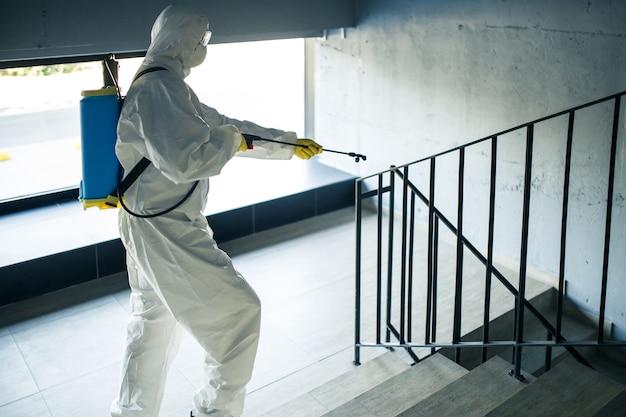 Ontsmettende werknemer die de trap in het winkelcentrum opruimt met een ontsmettingsmiddel om verspreiding van covid-19 te voorkomen. een man in een desinfectiepak spuit trappen. gezondheidszorg, quarantaine en hygiëneconcept.