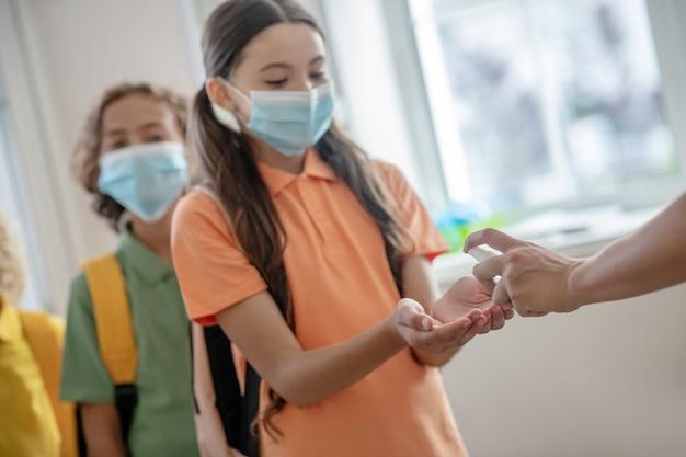 Ontsmettingsmiddel. donkerharig meisje met preventief masker dat wat ontsmettingsmiddel in haar hand krijgt