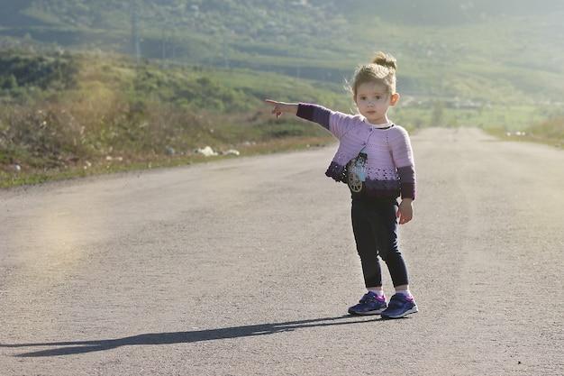 Ontsnap aan kinderen uit het huis - klein meisje liftend op de weg.