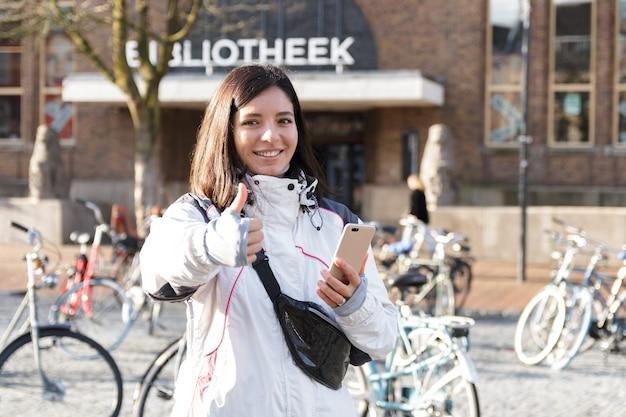 Ontsnap in een stad. jonge etniciteit vrouw in het vroege voorjaar met behulp van een telefoon om zichzelf op straat te begeleiden.