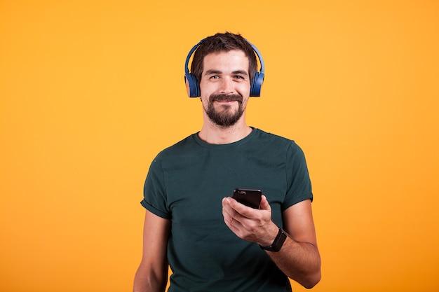 Ontspan aantrekkelijke man met blauwe koptelefoon en smartphone in zijn handen op oranje achtergrond in studio