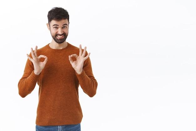 Ontspan alles goed. portret van zelfverzekerde knappe bebaarde man verzekert dat je op hem kunt rekenen, goede tekens laat zien, glimlacht, garandeert de beste kwaliteit en bevredigend resultaat, beveel product aan