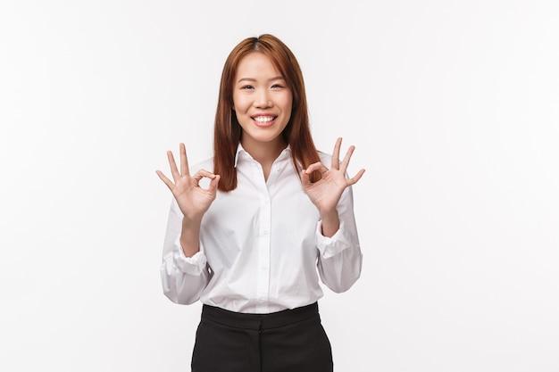 Ontspan, alles oké. vrolijke en zorgeloze aziatische vrouw zegt geen probleem, maakt een ok gebaar en glimlacht, verzekert alles wat is gedaan, ondertekende deal, garandeert een geweldige service en kwaliteit,