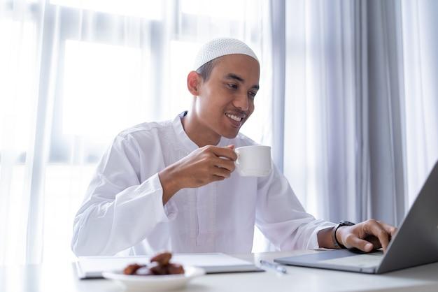 Ontspan aziatische musim man met een kopje koffie terwijl hij thuis werkt met behulp van een laptop