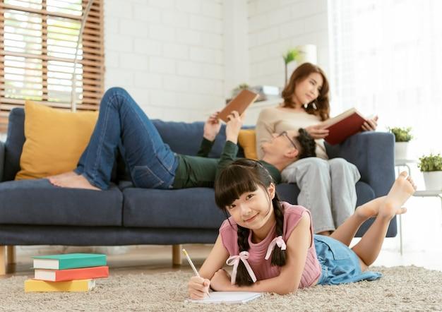 Ontspan aziatische ouder die een boek op bank leest en dochter die kunst in huiskamer schildert.