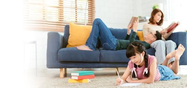 Ontspan aziatische ouder die een boek op bank leest en dochter die kunst in woonkamer thuis schildert. panoramische achtergrond.