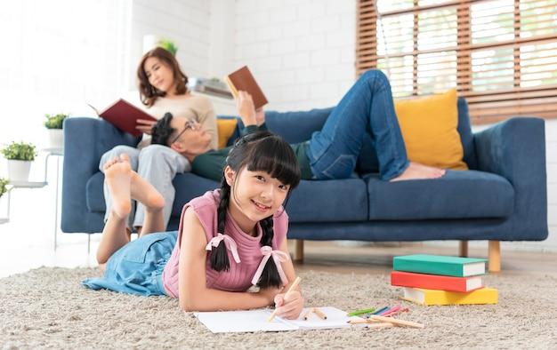 Ontspan aziatische ouder die een boek op bank leest en dochter die kunst in woonkamer thuis schildert