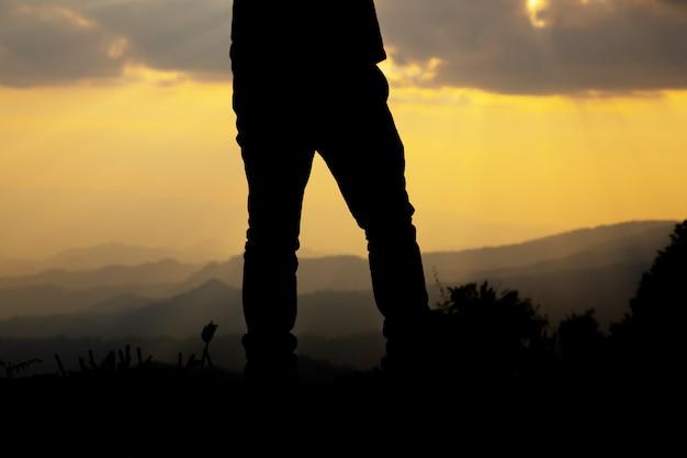 Ontspan de mens op heuvel bij zonsondergangsilhouet.