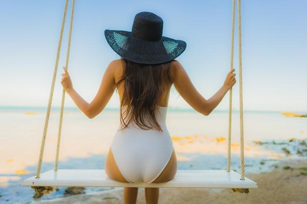 Ontspan de portret mooie jonge aziatische vrouwenzitting op de schommeling rond strand overzeese oceaan voor