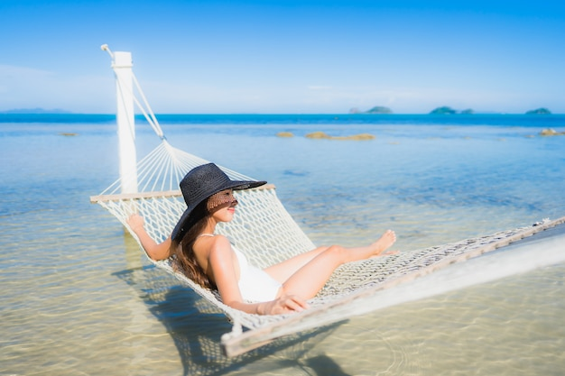 Ontspan de portret mooie jonge aziatische vrouwenzitting op hangmat rond overzeese strandoceaan voor