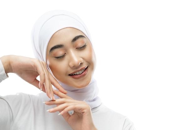 Ontspan de pose van een mooie hijab-vrouw die een witte sluier draagt wanneer ze haar ogen sluit met copyspace
