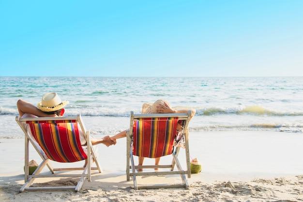 Ontspan het paar bepaalt op strandchiarrie met overzeese golf - de man en de vrouw hebben concept van de vakantie het op zee aard