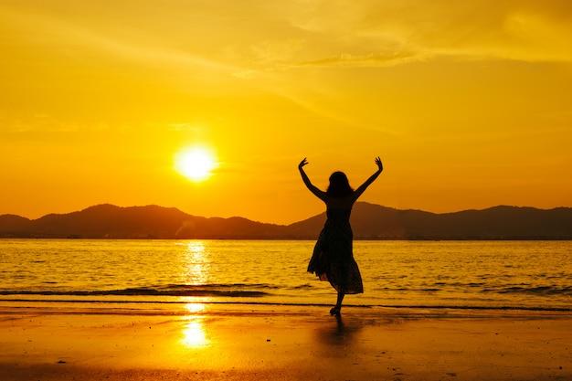 Ontspan het springen van de vrouw overzees op het strand