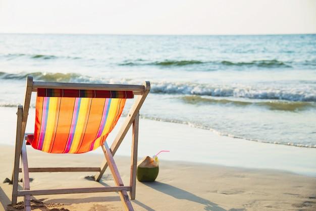 Ontspan ligstoel met verse kokosnoot op schoon zandstrand met blauwe overzees en duidelijke hemel - de overzeese aard ontspant concept