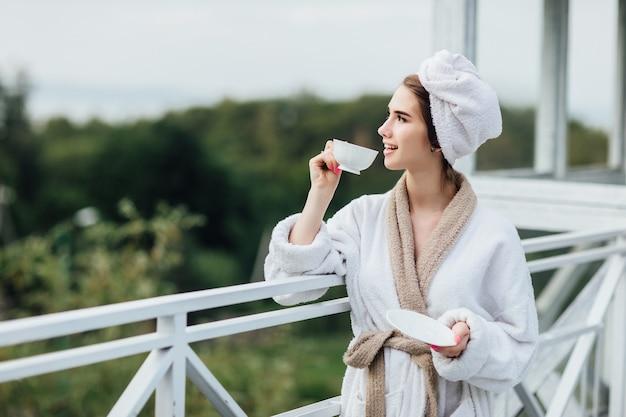 Ontspan op de bergen. jong, glimlachend meisje heeft een weekendtijd en houdt een kopje thee vast, mooie ochtend.