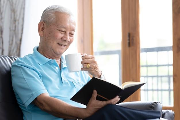 Ontspan oudere man zittend op de bank en interessant boek lezen in de woonkamer. pensioen levensstijl concept.