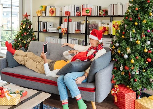 Ontspan senior paar in kerstmuts zittend op de bankbank en op schoot videobellen familie online met behulp van tablet thuis met kerstboom. contact houden met kleinkinderen op vakantie.