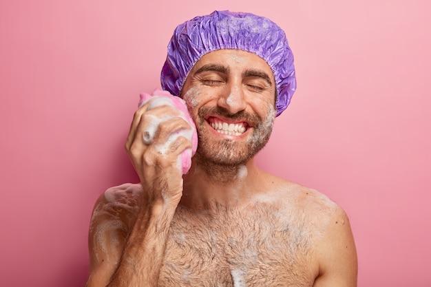Ontspan, spa, hygiëne, zachtheid concept. blije glimlachende jonge man met brede glimlach, toont witte perfecte tanden, wrijft wang met spons, heeft schuim op lichaam