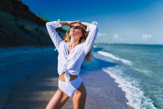 Ontspan tijd elegante vrouw rust op het strand mooie vrouwelijkheid blond haar dame rust en vrijheid concept