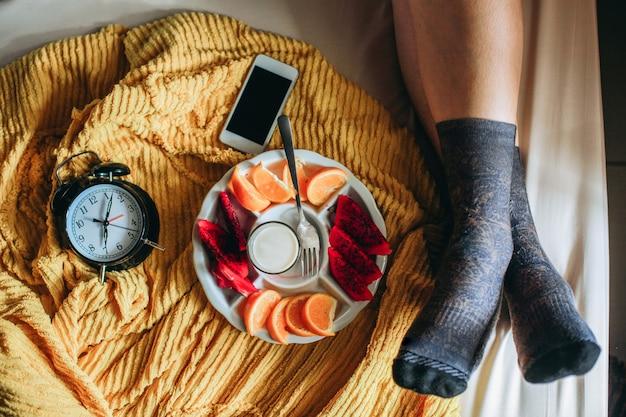 Ontspan voet in sokken op het bed met diverse fruitwekker en smartphone aan de zijkant