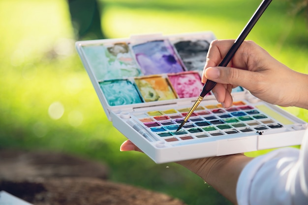Ontspan vrouw het schilderen het kunstwerk van de waterverfkunst in groene tuin bosaard
