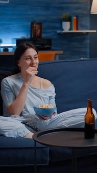Ontspan vrouw in pyjama die popcorn eet en tv kijkt