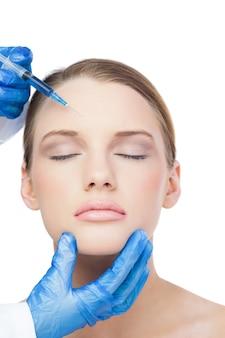 Ontspannen aantrekkelijk model met botox injectie op het voorhoofd