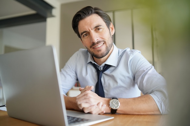 Ontspannen aantrekkelijke zakenman die in modern bureau werkt