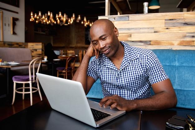 Ontspannen afrikaanse mens bij een koffielijst die laptop met behulp van