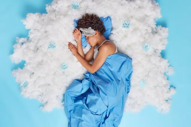 Ontspannen afro-amerikaanse vrouw met krullend haar slaapt goed en heeft zoete dromen