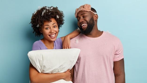Ontspannen afro-paar lacht oprecht, staat naast elkaar, drukt goede emoties uit na een goede nachtrust, heeft lang geslapen, kussen vastgehouden, geïsoleerd over blauwe muur. heerlijke tijd om te slapen