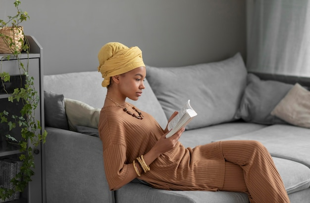 Ontspannen arabische vrouw die thuis een boek leest Gratis Foto