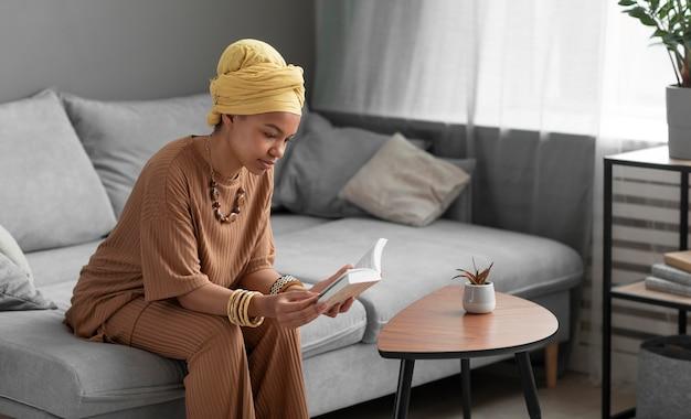 Ontspannen arabische vrouw die thuis een boek leest