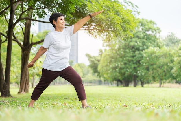 Ontspannen aziatische hogere vrouw in witte doek die uitrekkende training doet haar wapens bij park. glimlachend bejaard thais wijfje die buiten van het uitoefenen op aard genieten