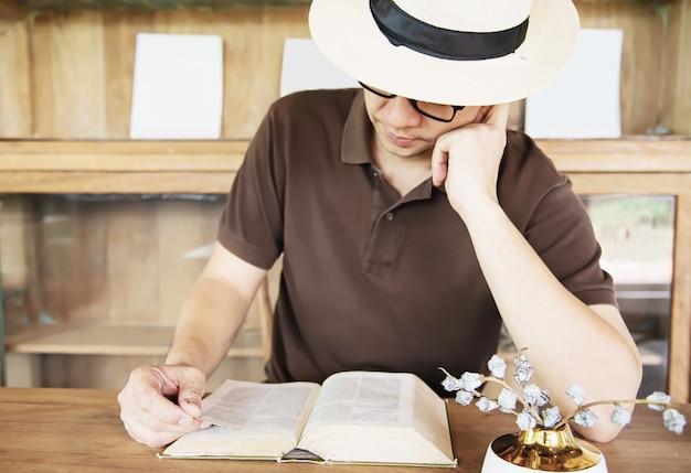 Ontspannen aziatische man die een boek leest
