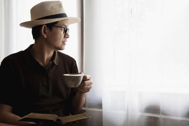 Ontspannen aziatische man drinken van een kopje koffie en het lezen van een boek