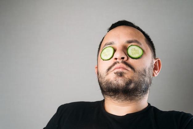 Ontspannen bebaarde jongeman met een hydraterend komkommermasker op zijn gezicht