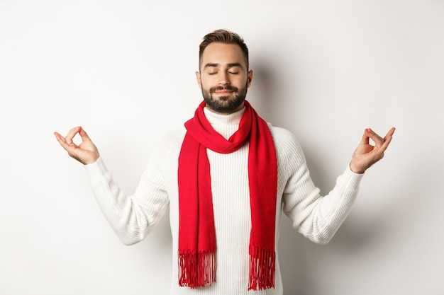Ontspannen bebaarde man die in vrede staat, mediteert met gesloten ogen, staande op een witte achtergrond in rode sjaal en trui