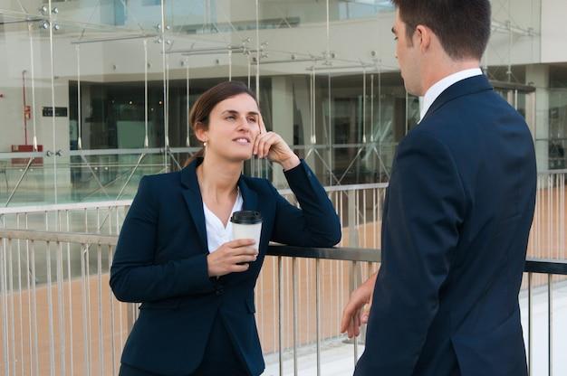 Ontspannen bedrijfsman en vrouw die in openlucht babbelen