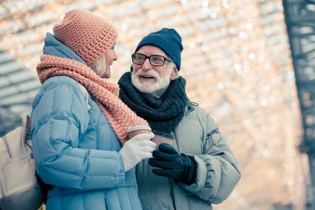 Ontspannen bejaarde echtpaar in winterkleren die samen staan en praten. kerstverlichting op de achtergrond