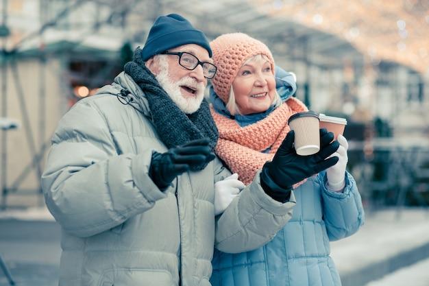 Ontspannen bejaarde echtpaar in winterkleren tijd buitenshuis doorbrengen met kartonnen kopjes koffie in hun handen en wegkijken met een glimlach