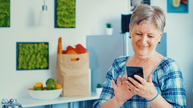 Ontspannen bejaarde vrouw browsen op de telefoon in de keuken tijdens het ontbijt. authentieke bejaarde die moderne smartphone-internettechnologie gebruikt. online communicatie verbonden met de wereld, senioren vrije tijd t