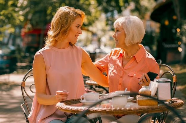 Ontspannen bejaarde vrouw die buiten aan de cafétafel zit met haar dochter