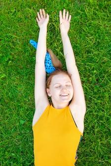 Ontspannen blanke jonge vrouw liggend op het gras met armen omhoog