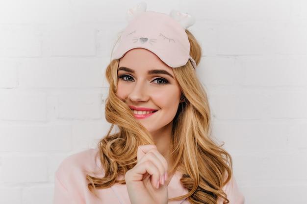 Ontspannen blauwogige vrouw in roze eyemask die op lichte muur lacht. foto van extatisch meisje met blond golvend kapsel draagt slaapmasker.