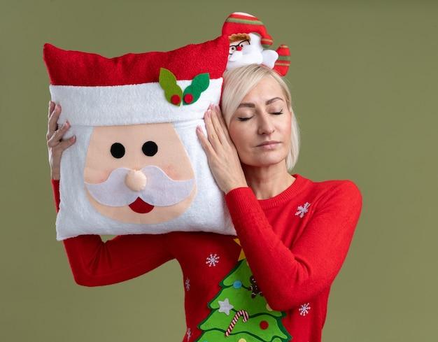 Ontspannen blonde vrouw van middelbare leeftijd die de hoofdband van de kerstman en de kersttrui draagt die het hoofd van de kerstman aanraken met het met gesloten ogen geïsoleerd op olijfgroene achtergrond