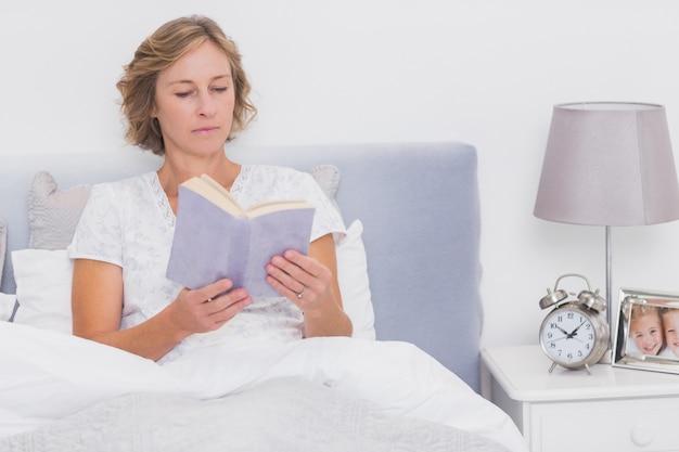 Ontspannen blonde vrouwenzitting in bedlezing