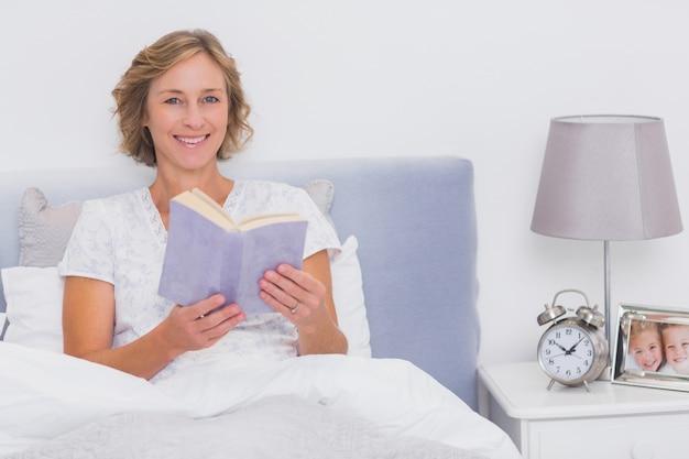 Ontspannen blonde vrouwenzitting in het boek van de bedholding